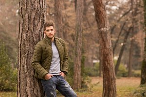 young man autumn park forest posing