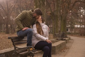 young couple sitting park bench kiss