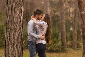 young couple kissing park loving