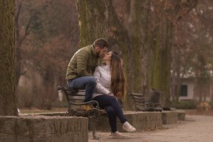 young couple kissing park sitting