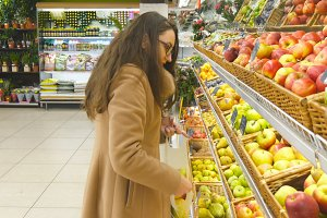 Woman selecting fresh red apples in grocery store produce department and putting it in plastic bag. Young pretty girl is choosing apples in supermarket and putting them into shop basket. Close up