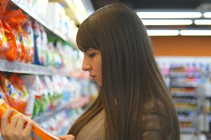 Young woman choosing household chemicals in supermarket. Beautiful girl selects fabric softener or washing powder at the store. Department of cleaning product and home care. Close up