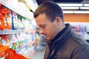 man choosing household chemicals