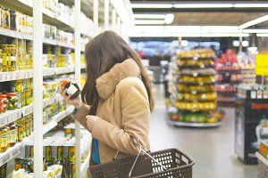 Young woman with shopping cart coming up to shelves in shop and taking product from it. Beautiful girl select delicious canned olives at store and putting it into the basket. Close up