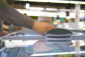 Female hands opening glass door in the refrigerated section at the supermarket and choosing ice cream. Young woman taking product from fridge in shop and putting it into the basket. Close up