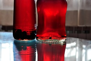 two bottles with berries liquor
