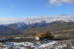 Crawler tractor with grederom against the backdrop of snow-capped mountains
