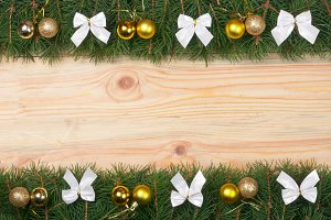 Christmas frame made of fir branches decorated with white bows and golden balls on a light wooden background