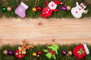 Christmas frame made of fir branches decorated with balls Snowman and Santa Claus on a light wooden background
