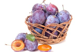 plum in a wicker basket isolated on white background