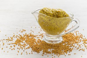 French mustard sauce and mustard seeds on white background