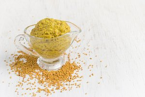 French mustard sauce and mustard seeds on white background, copy