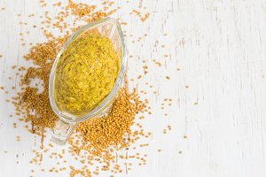 French mustard sauce and mustard seeds on white background. Top