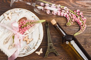 Pink lupins and tableware on the wooden table