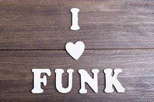 White letters laying on dark wood messaging I love funk. Horizontal studio shot