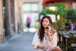 Portrait of beautiful woman sitting in outdoor cafe drinking coffee and talking by smartphone.