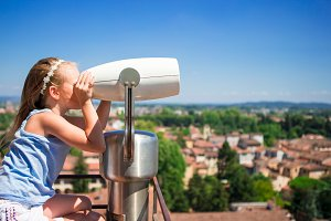 Little girl looking at coin operated binocular on terrace at small town in Tuscany, Italy