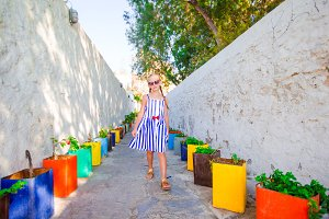 Cute girl in dress at street of typical greek traditional village on Mykonos Island, in Greece