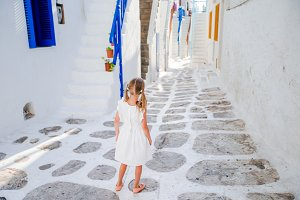 Little girl in white dress in old streets at Mykonos.