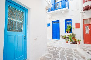 Traditional houses withe blue doors in the narrow streets of Mykonos, Greece.