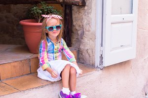 Adorable little girl in outdoors cafe in European city
