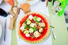 Delicious fresh greek salad served for lunch in watermelon at outdoor restaurant