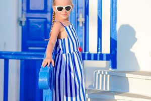 Little adorable girl in dress outdoors in old streets an Mykonos. Kid at street of typical greek traditional village with white walls and colorful doors on Mykonos Island, in Greece
