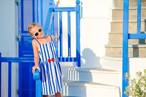 Little adorable girl at street of typical greek village with white walls and colorful doors on Mykonos