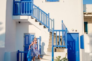 Typical house with blue balconies, stairs and flowers. Little girl on stairs in traditional greek house. Beautiful architecture building exterior with cycladic style.