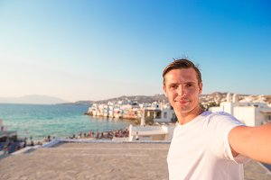 Young man taking selfie portrait background Little Venice in Mykonos