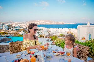 Family having breakfast at outdoor cafe with amazing view on Mykonos town. Adorable girl and mom drinking fresh juice and eating croissant on luxury hotel terrace
