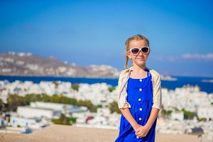 Little girl in blue dress outdoors. Kid at street of typical greek traditional village with white walls and colorful doors on Mykonos Island, in Greece