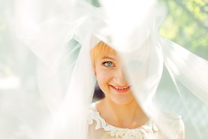 Blue-eyed bride smiles under a veil