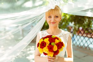 Bride looks shy holding a bouquet