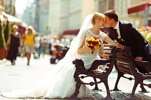 Bride and fiance kiss on old benches