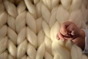 Hand Dyed Merino Wool with baby hand. Close-up of knitted blanket, merino wool background