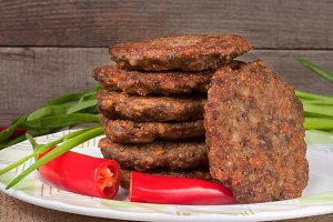 liver pancakes or cutlets with chili pepper and green onions on a wooden background
