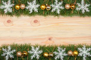 Christmas frame made of fir branches decorated with snowflakes and gold balls on a light wooden background