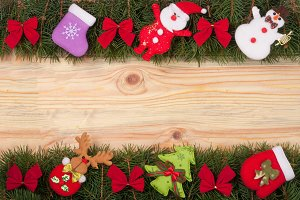 Christmas frame made of fir branches decorated with red bows Snowman and Santa Claus on a light wooden background