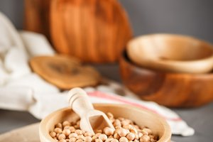 Chickpeas in a wooden bowl on gray background