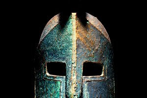 Ancient greek Sparta style helmet replica isolated on a black background, studio shot.
