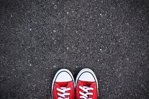 Red sneakers on road background