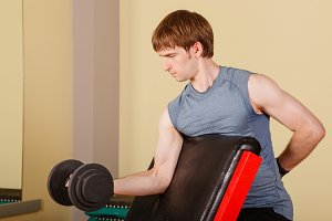 Man exercise biceps with dumbbell