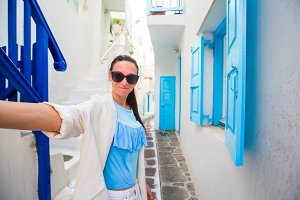 Happy woman taking selfie on deserted streets of greek village. Young beautiful woman on vacation exploring european city