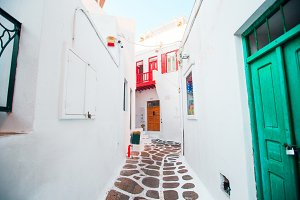 The narrow streets of greek island with white balconies, stairs and colorful doors. Beautiful architecture building exterior with cycladic style.