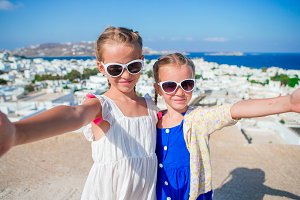 Two girls taking selfie photo outdoors with amazing view on greek village and sea