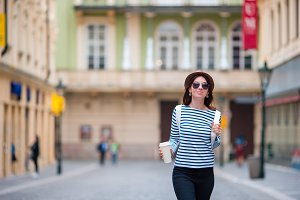 Beautiful woman drinking coffee in Europe. Caucasian tourist enjoy her european vacation in empty city
