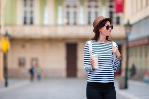 Young woman walking on the city and drinking coffee in Europe. Caucasian tourist enjoy her european vacation in empty city