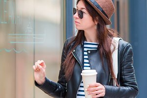 Girl drinking coffee in european city outdoors. Caucasian tourist enjoy her european vacation in empty city