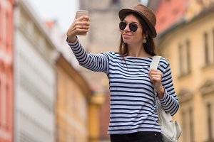 Happy girl taking selfie background famous castle in european city. Caucasian tourist walking along the deserted streets of Europe.